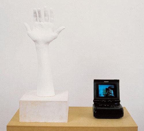 Eric Duyckaerts, La main à 2 pouces, Base 12 1993. Plâtre, écran vidéo, bois.