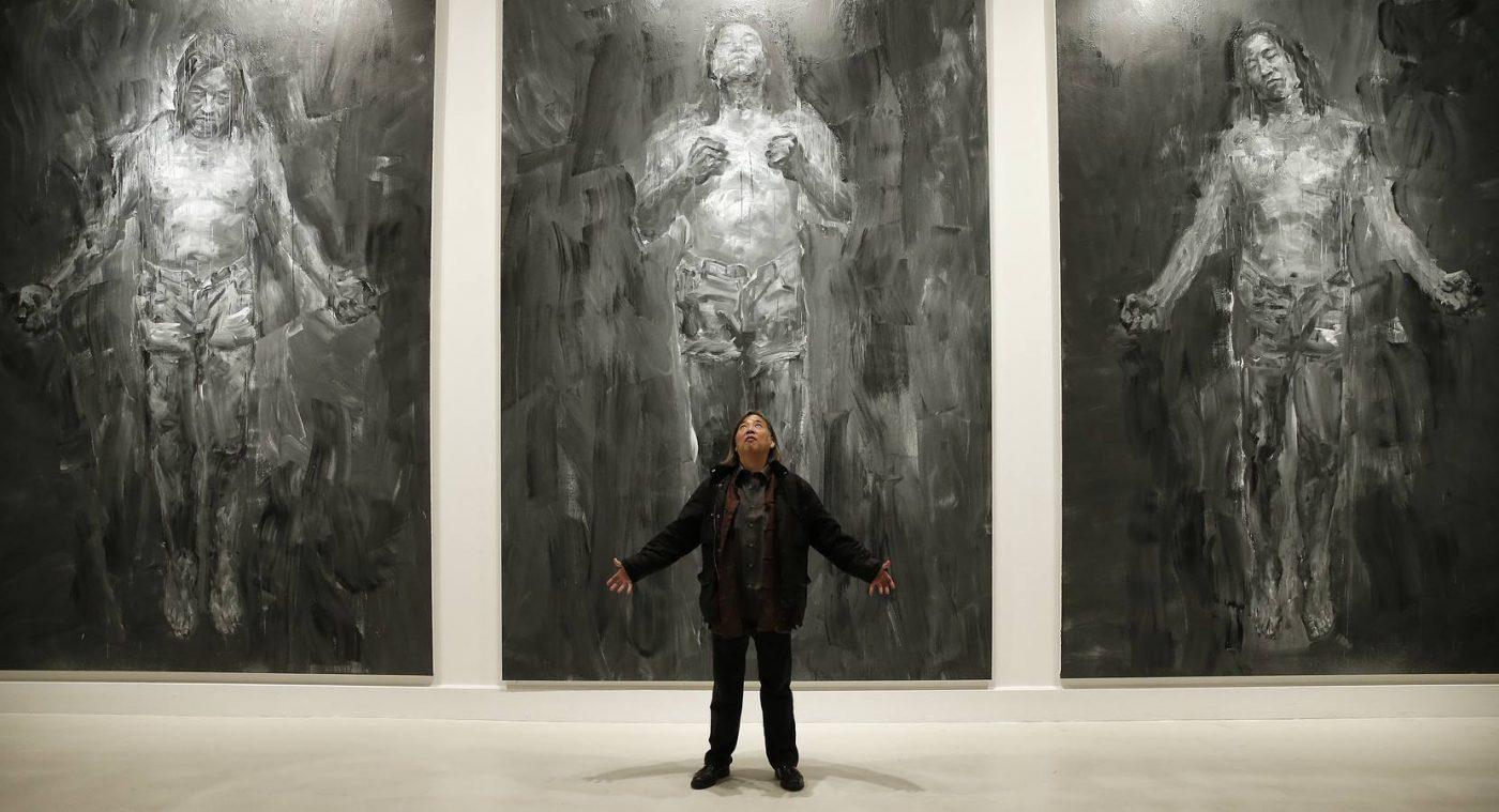 Yan Pei-Ming implorant, devant ses tableaux monumentaux