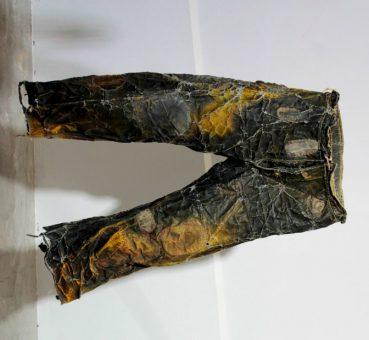 Cécile Borne, Pantalon, le ciré se craquelle, le jaune disparaît. On devine sur les genoux des trous rapiécés. © Coline Jacquet