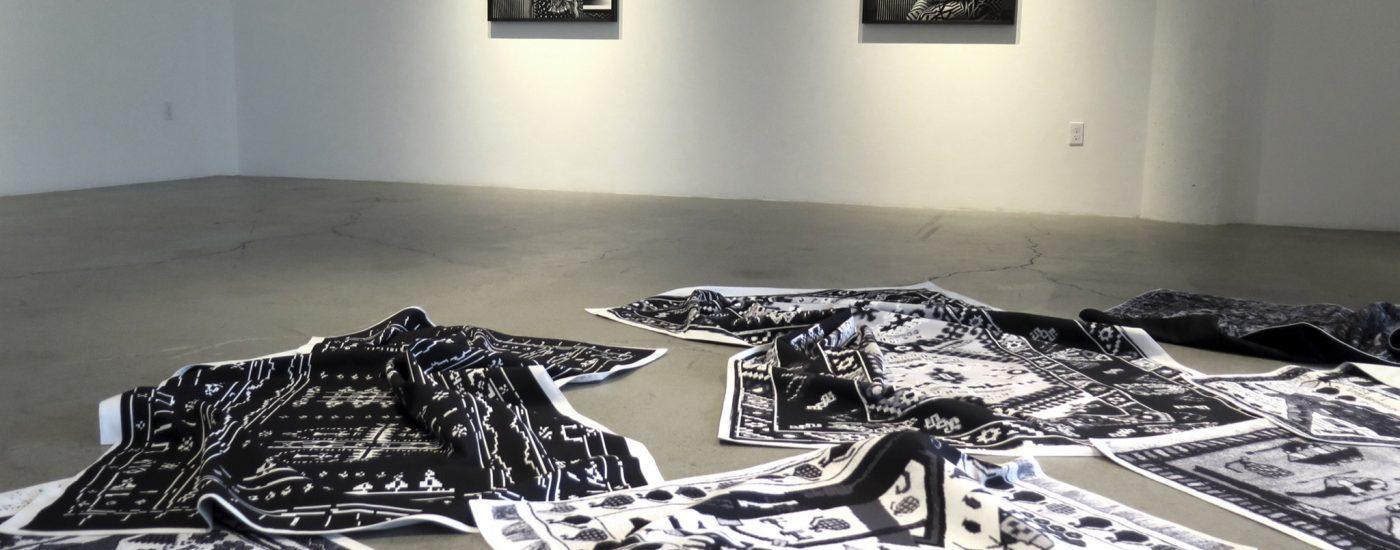 """Stephanie Syjuco, Vue de l'installation, """"Lossy RIPS"""" avec la charte graphique au mur."""