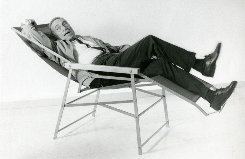 Photo de Achille Castiglioni se détendant sur une chaise longue pliante.